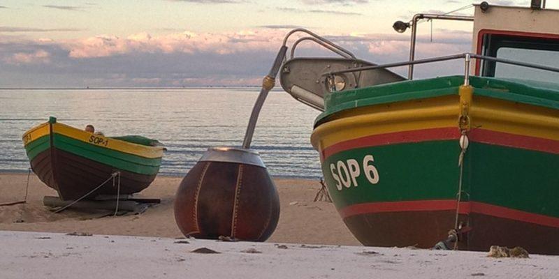 plaża, łodzie i tykwa z bombillą i yerba mate od yerba mamy